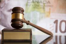 Un marteau de justice sur un bloc en bois avec une plaque de cuivre devant un billet de cent dollars canadien.